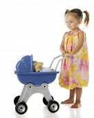 An adorable preschooler walking her rag doll in a toy baby buggy.  On a white background.