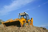 stock photo of heavy equipment operator  - yellow bulldozer at work on the ground - JPG