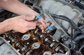 stock photo of overhauling  - Car mechanic fixing fuel injector at two camshaft gasoline engine - JPG