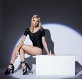 Attractive leggy blonde posing in spotlight