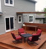 stock photo of red siding  - Backyard deck with deck furniture table and chairs.