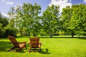 image of lawn chair  - Two wooden adirondack chairs on lush green lawn with trees - JPG
