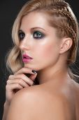 Portrait of young beautiful woman with bright fashion makeup, manicure and creative hairstyle with t
