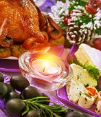 Christmastime banquet, festive table setting with bright candle light, New Year eve, tasty baked chicken, black olives, pine cone with snow decoration