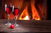 Wine glasses and a heart on the background of the fireplace.