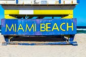 image of beach hut  - wooden life guard huts in art deco style at south beach with MIAMI BEACH sign - JPG