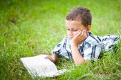 Cute Kid Reading A Book Outdoor