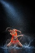 picture of dancing rain  - Woman dancing under rain in orange dress - JPG