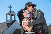 stock photo of crossed pistols  - Romantic Old West Man and Woman Embrace - JPG