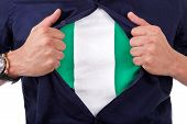stock photo of nigeria  - Young sport fan opening his shirt and showing the flag his country nigeria nigerian flag - JPG