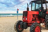 old red tractor on the sandy beach
