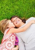 Happy mother and daughter relaxing outside on green grass. Spending quality time together, Real emot