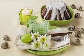 stock photo of quail egg  - Easter table setting with chicken quail eggs and flower next to a burning candle - JPG