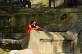 Holy Sadhu Man Singing On Flute In Pashupatinath, Nepal