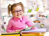 stock photo of spectacles  - Happy child girl in glasses reading books in library - JPG