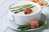 foto of white asparagus  - Asparagus cream soup with ham closeup in white bowl and croutons - JPG