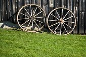 picture of wagon wheel  - Two wagon wheels lie up against a building on a bright sunny day - JPG