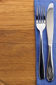 knife and fork at napkin on wooden board