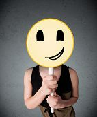 Young lady holding a yellow smiley face emoticon in front of her head