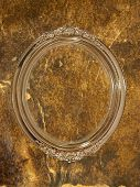 Golden oval photo frame with empty space inside