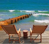 Comfortable lounge chairs on wooden platform for rest and observation. Breakwater of the emerald sea