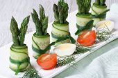 Rolls Of Fresh Cucumber With Green Asparagus On A Plate