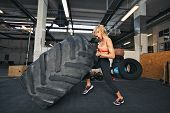 picture of gym workout  - Muscular young woman flipping tire at gym - JPG