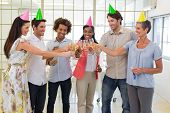 Coworkers celebrate success with champagne and a party in the office