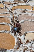 MARAS, PERU - JULY 23, 2013: woman at Maras salt mines in the peruvian Andes