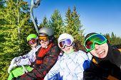 Smiling snowboarders in ski masks on elevator