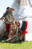 pic of wigwams  - Two North American Indians communicate near a wigwam - JPG