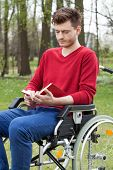Disabled Man Reading A Book In Garden
