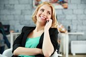 Young happy woman talking on the phone at office
