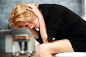 Upset beautiful woman sitting on the office chair touching her head
