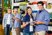 Portrait of happy couple holding tool set in hardware store with customers in background