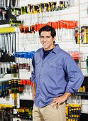 Portrait of male customer with hands on hip smiling in hardware shop