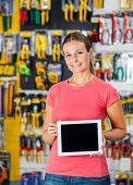 Portrait of smiling woman presenting digital tablet in hardware shop