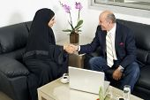 stock photo of hijabs  - Senior Businessman Shaking hands with Woman wearing hijab - JPG
