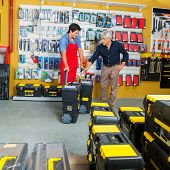 Young salesman showing tool cases to male customer in hardware store
