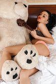 woman lying bed with big teddy bear