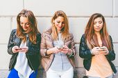 picture of adolescent  - Girls typing on mobile phones  - JPG