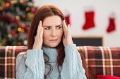 Woman getting a head ache at christmas at home in the living room