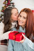 Daughter giving her mother a christmas present at home in the living room