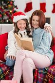Festive mother and daughter reading on the couch at home in the living room