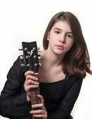 Young brunette teen girl playing acoustic guitar