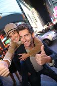 Couple showing thumbs up in Time Square by night
