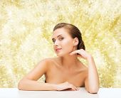beauty, health and people concept - smiling beautiful woman with clean perfect skin over yellow lights background