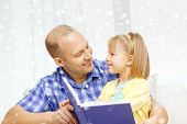 family, children, education and happy people concept - smiling father and daughter reading book at home