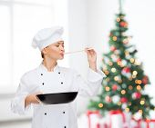 cooking, holidays, people and food concept - smiling female chef with pan and spoon tasting food over living room and christmas tree background