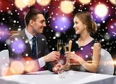 celebration, christmas, holidays and people concept - smiling couple clinking glasses of sparkling wine at restaurant over night lights background
